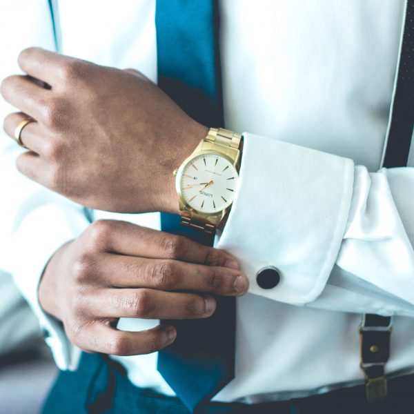 A gold watch on a mans wrist